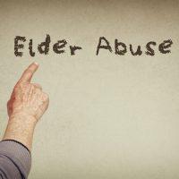 Finger pointing at handwritten sign elder abuse