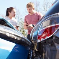 two drivers exchanging insurance info after accident