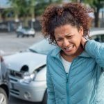 Woman suffering whiplash after bad cars pile up