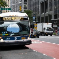"""New York, New York, USA - July 15, 2020: An MTA bus displaying """"MASKS REQUIRED"""" during the Covid-19 pandemic. People can be seen in the background."""